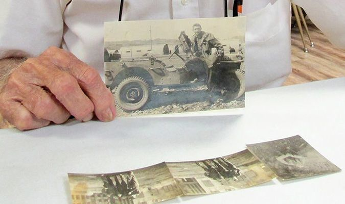 Willard Wayne Stallings holds a picture of himself in a Jeep while serving in uniform.  Stallings, 94, still lives on Stallings Road in New Summerfield.  Photo by Deborah Burkett