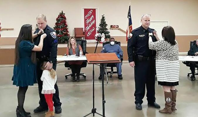 The spouses of Chase Berryhill (left) and Nathan Acker (right) do the honors during a Dec. 17 pinning service held during the Rusk City Council meeting at the Rusk Civic Center. Acker was promoted to lieutenant, while Berryhill was named a sergeant.   Photo by Jo Anne Embleton