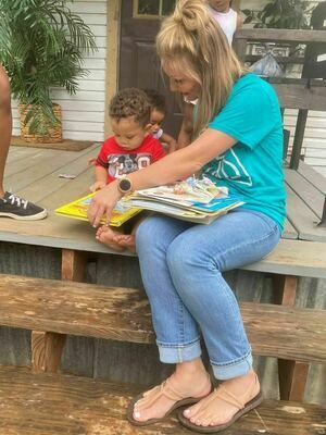A Rusk Elementary School teacher visits with a toddler Aug. 2, sharing a handful of books as part of a project designed to foster a love for reading that ultimately creates bonds between students, their families and the school staff.   Courtesy photo