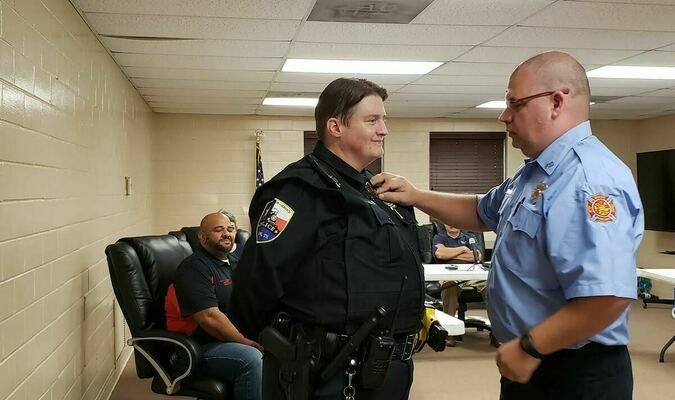 Shawn Solly, Rusk Police Department's newest officer, is pinned by her husband Phillip, during an Oct. 14 Rusk City Council meeting.  Photo by Jo Anne Embleton