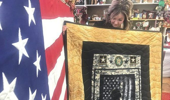 At The Fabric House Saturday, owner and veterans quilt project organizer Susan Downs-Freeman pauses to look at one of the veterans' gifts — an Army Silhouette lap quilt — as she prepared for Veterans Day presentation ceremonies Monday.  JENAY TATE PHOTO