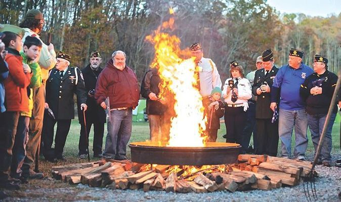 Local veterans commit retired flags to the flames.   MICHELLE MULLINS PHOTO