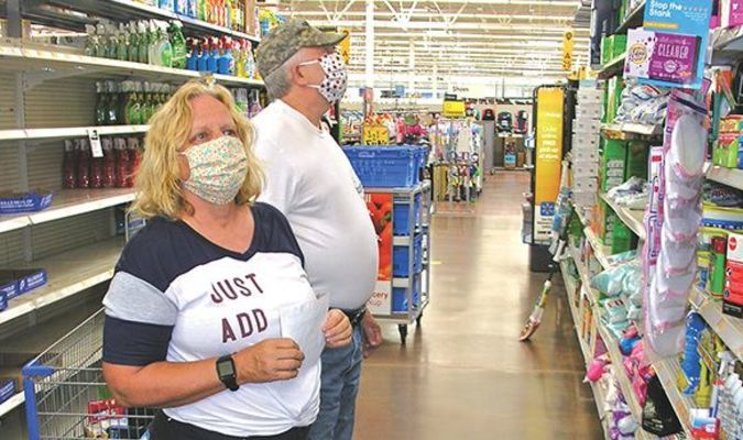 Two customers at the Norton Walmart comply with the mask requirement while shopping shortly after noon Friday. By a reporter's observations, roughly half the customers inside were not wearing any face covering.  JEFF LESTER PHOTO