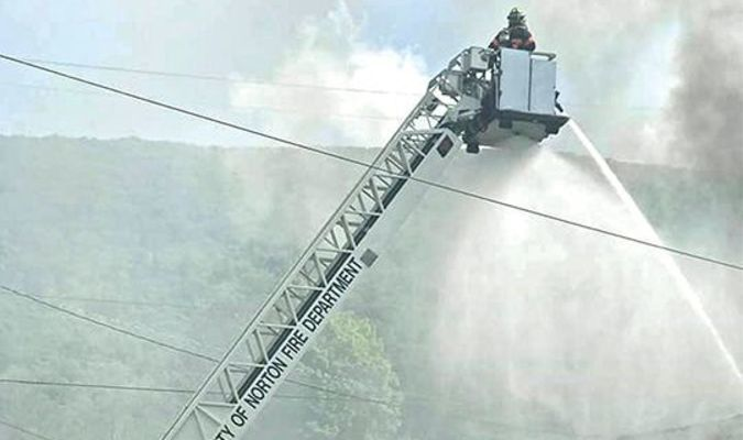 Norton Fire Department uses its aerial apparatus Thursday to attack the building fire in Ramsey.  NORTON FIRE DEPARTMENT PHOTO