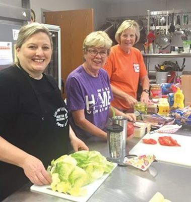 Volunteers, who make up their cook team, prepare a hearty breakfast each morning at 7 am in the church fellowship hall. Afterwards, this team prepares lunches for all work crews. Another group of volunteers then deliver these lunches to each job site.