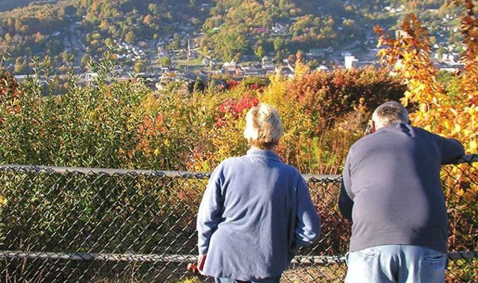These two folks were among several Flag Rock visitors Wednesday afternoon, and they took turns concentrating intently on trying to get a perfect photo of the flag on the rock. The man said he believed the fall colors at that elevation were about two days away from hitting their peak.  JEFF LESTER PHOTO