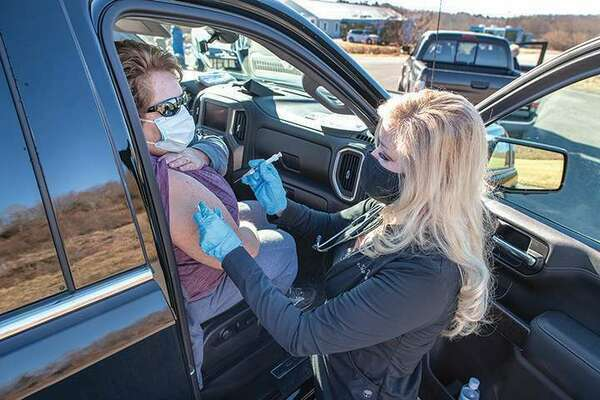 The Health Wagon finally received its first shipment of the Moderna COVID-19 vaccine this week and began putting shots in arms, according to president and chief executive Teresa Tyson, shown here administering the vaccine during a drive-through clinic. 'The response has been overwhelming as cars lined up with eager folks to get their first shot,' Tyson noted in a Thursday email.  TIM COX PHOTO