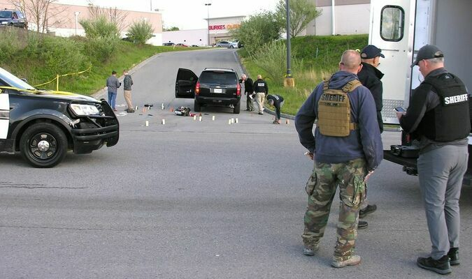 Investigators process evidence around city police Chief James Lane's vehicle at an entrance point to the Norton Commons Shopping Center. JEFF LESTER PHOTO