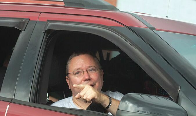 Norton Police Chief James Lane points at a well-wisher Friday during a parade welcoming his release from the Norton Community Hospital rehabilitation unit. He was released to go home to finish recovery from being shot May 7 while responding to a shoplifting call. ELISSA POWERS PHOTO