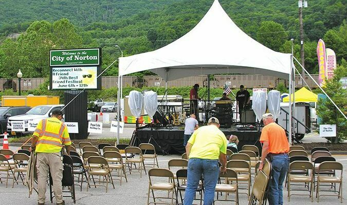 Norton workers set up chairs Wednesday afternoon for a Best Friend Festival concert while hoping the intermittent rain showers would hold off awhile. Unfortunately, the nasty weather is expected to continue today and part of Saturday.  JEFF LESTER PHOTO