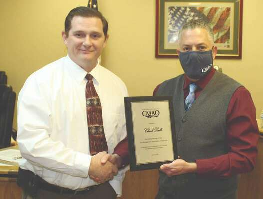 Dave Slezickey (right), president of City Managers Association of Oklahoma (CMAO) presents a plaque to city manager Chuck Ralls in recognition of Ralls completing the course work to become an accredited manager of the CMAO. The presentation was made at the city council meeting last Tuesday. Slezickey praised Ralls' work in the program.