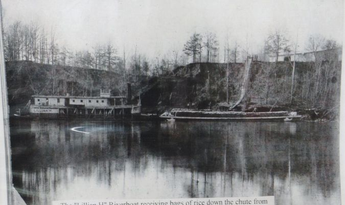 """The caption states: The """"Lillian H"""" Riverboat receiving bags of rice down the chute from the Prange-Tindall Warehouse on top of the bluff. Year unknown, but certainly dated no later than 1923"""