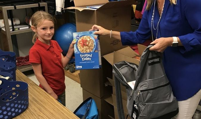 Avery helps DES Counselor, Lori Wilson stuff back packs