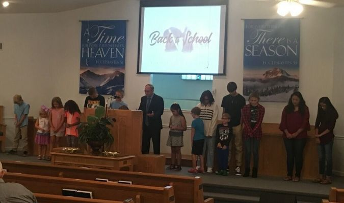 County Judge and Preacher Eddie Best pray with the students of his congregation at Gillett Baptist.