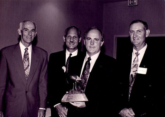 Richard Mason of the Arkansas Wildlife Federation presenting award to Chuck Dees, Bill Spicer, and Hugh Cockrell of Waste Management