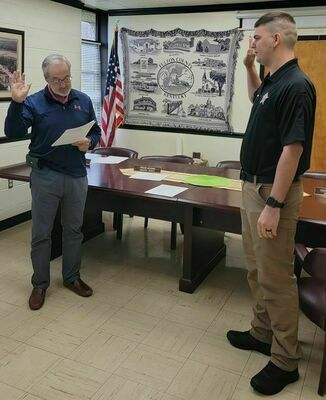 SWEARING IN - Austin Matheny, right, is shown being sworn in as a new Fulton County Sheriff's Deputy, by Fulton County Judge/Executive Jim Martin, on April 23. (Photo submitted)