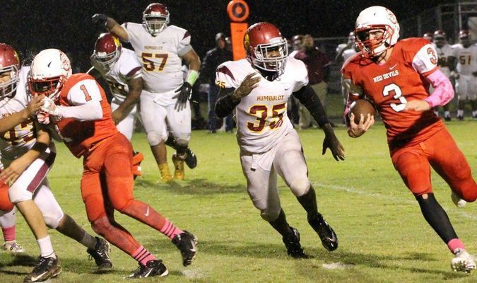 BIG NIGHT FOR BIG RED --South Fulton running back Dalton Gray uses a block from team mate Michael Reeves on a touchdown run in the third quarter Friday night. Gray scored three touchdowns against Humboldt on the Devils' home field, posting a 54-12 win. (Photo by Charles Choate)