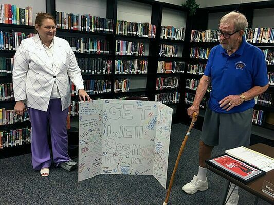 """RETURNING FOR THE KIDS – Bill Robertson recently responded as to why he came back on the Fulton Independent School Board after serving for so many years and then retiring. Superintendent DeAnna Miller, left, holds a card given to Robertson, made and signed by the Fulton High School students when he was very ill, and given to him. """"The kids…that's why I am doing this again,"""" he said."""