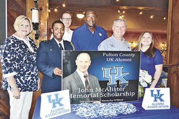 "BIG BLUE BENEFICIARIES – Tristan Roberson, second from left and Sarah Gardner, far right, were awarded $1,000 scholarships May 31, by the Fulton County University of Kentucky Alumni group, during the organization's annual Scholarship Banquet held at The Keg restaurant in Fulton. Gardner, a Hickman County High School graduate, received the scholarship for the second time, and will be returning to UK, as an English major. Roberson, who was home schooled, will return to UK as a junior this Fall. Anyia Jones, a 2018 Fulton High School graduate was also a scholarship recipient but was unable to attend the banquet. Those interested in contributing to the scholarship fund may forward donations to Bob Mahan or Mallory Worley at Heritage Bank of Fulton. The scholarships are named in honor of longtime UK supporter, the late John McAlister. Also pictured, from left are Brenda Mahan, scholarship coordinator, Roberson, Tim Walsh, UK Alumni Association, guest speaker and former UK standout, Jack ""Goose"" Givens, Fulton County UK Alumni president Alan Jones and Gardner. Over 90 people attended this year's banquet. (Photo by Benita Fuzzell)"