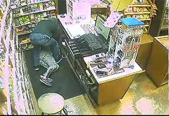 ARMED SUSPECT SOUGHT – This video surveillance footage captured by security cameras at 501 Liquors on Martin Luther King, Jr. Drive in Fulton, shows a male suspect forcing a store clerk to the floor, wielding a handgun, before fleeing on foot with cash from the register. (Photo submitted.)