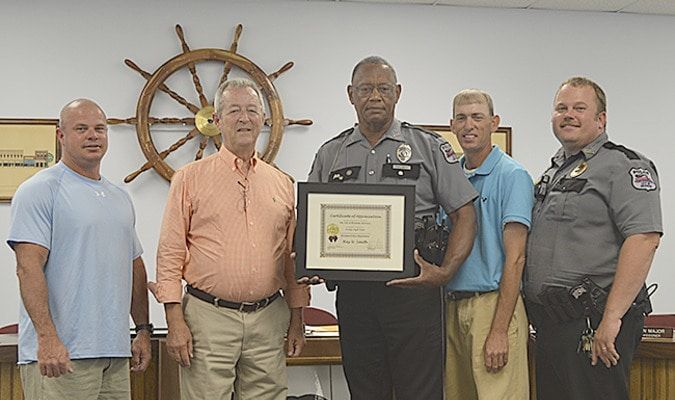"SERVICE APPRECIATED – The Hickman City Commission presented Police Officer Ray Smith with a Certificate of Appreciation for recognition of 28 years of service to the Hickman Police Department at the City Commission meeting June 11. Smith said, ""I never thought it would be 28. It has been some hard days and some good days and if I had it to do over again I still would become a police officer. It is in my blood."" Smith has also served in the National Guard and regular Army for 20 years. Smith received three DD214 as a Vietnam veteran, Persian Gulf, and Iraq, serving in the Navy. From left are Commissioner Heath Carlton, Mayor David Lattus, Smith, Commissioner Phillip Williams, and Hickman Chief of Police Tony Grogan. (Photo by Barbara Atwill)"