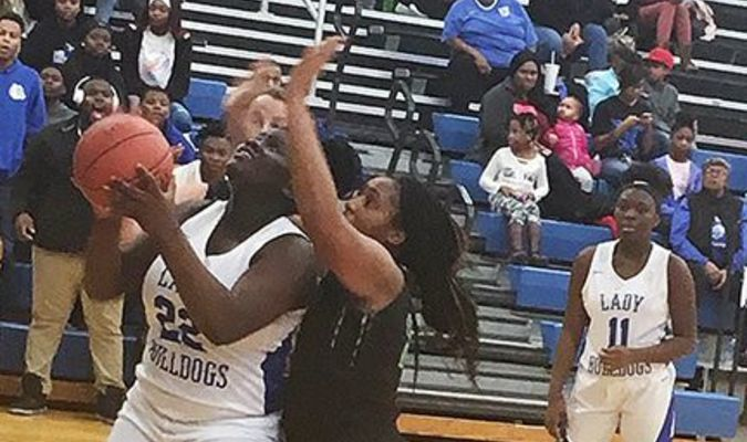CROWDING THE BASKET – Fulton High School Lady Bulldog Takyra Taylor fights off a Lady Falcon defender during the contest at FHS Monday evening and team mate Ca'Tya looks on. The Lady Bulldogs won, 42-33. (Photo by Benita Fuzzell.)