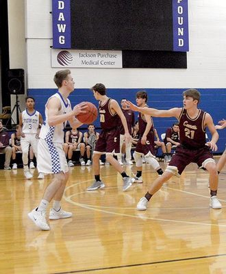 KEEPING IT FROM CARLISLE – Fulton Bulldog Cameron Madding searches out a teammate during action at FHS against Carlisle Dec. 11. The Bulldogs were handed a defeat by the Comets 77-36. (Photo by Benita Fuzzell)