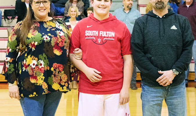 Dylan Ruddle, center, was honored recently at South Fulton Middle School's Eighth Grade Night for Basketball. Pictured with Ruddle are his parents Margaret Simmons and Rob Ruddle.