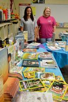 """CAMP REEL DIRECTORS -- South Fulton Elementary 'Camp Reel"""" Directors, Christa Hankins and Laura Murphy, look over the selections in the camp's """"cafe"""" of books, where students feast on their favorites, and even get to take home book choices throughout the camp, which lasts for four weeks. The camp was made possible through a Read to Be Ready Summer grant, and is free to SFES students who participate. (Photo by Benita Fuzzell.)"""