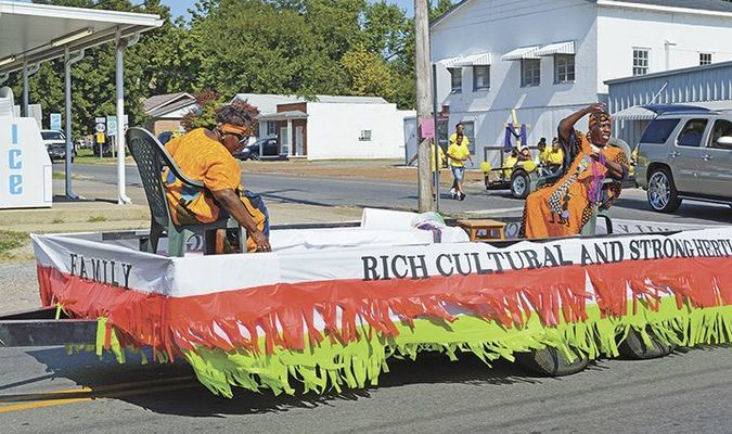 STRONG HERITAGE – The Eighth of August committee sponsored their annual parade Aug. 4 with several floats, cars, motorcycles, and more. The above float, Family - Rich Cultural and Strong Heritage, is shown with float riders tossing candy to viewers at the corner of Moscow Avenue and South Seventh St., in Hickman. (Photo by Barbara Atwill)