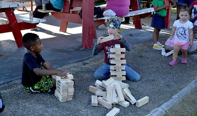 THEIR OWN FORM ON JENGA – Two young lads enjoyed their own version of Jenga at the Kid's Day at the Park Sept. 5. The 26th Annual Hickman Pecan Festival held the annual event in Jeff Green Memorial Park, where they served grilled hot dogs, chips, and drinks. Snow-cones and games of Jenga, water orbys, frisbee throwing and egg drop were enjoyed by those in attendance. (Photo by Barbara Atwill)