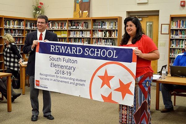 Tim Watkins, Director of Schools for Obion County's system, presented South Fulton Elementary Principal Laura Pitts with a banner for display honoring SFES as a 'Reward School'. (Photo by Benita Fuzzell)