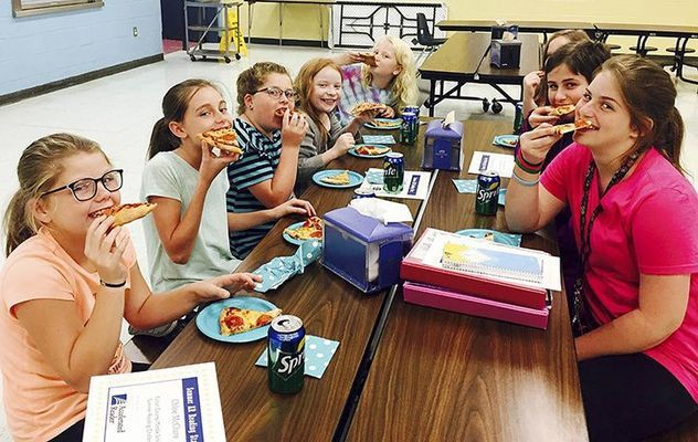 PIZZA REWARDS - Students enjoying a pizza party for accepting the Captain's Reading Challenge over the summer and reading multiple books included, clockwise from left, Chloe McClure, McKayden McClure, Emmarie Cermak, Alexis Edgin, Miriam Varden, Zoie Somerfield, Lily Hershberger, and Kally Hershberger. (Photo submitted)