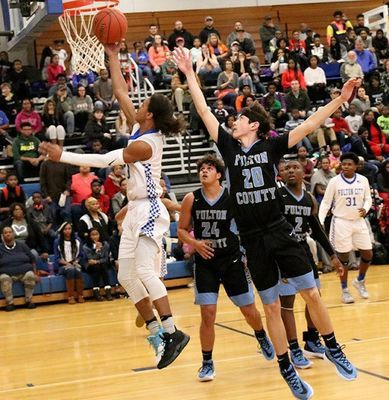 LAY-UP – Fulton County's Hayden Murphy (20) tries to defend the shot of Fulton City's Camarae Cobb (3), during the First District game played at Fulton. Cobb scored five points on the night, with the Bulldogs winning the cross-county match-up, 57-53. (Photo by Charles Choate)