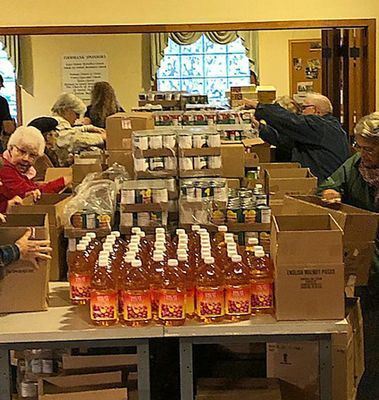 Foodbank volunteers sort and prepare the many boxes of food items distributed each month locally.