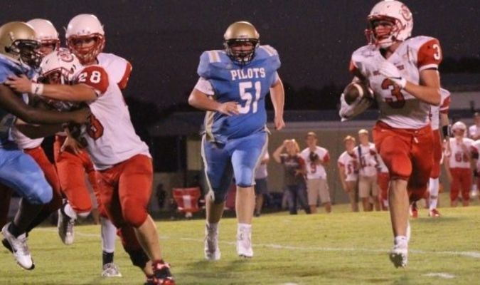 South Fulton's Dalton Gray runs wide, as Fulton County's Tyler Love pursues the play in action Friday night at the FCHS field. Gray was able to score a second quarter touchdown, but the Red Devils suffered a 62-16 loss at the hands of the Pilots. (Photo by Charles Choate.)