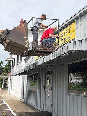 HERE'S THE SIGN – Mounting the sign for the relocated River Town Mission Thrift Store at 1232 Moscow Ave in Hickman are, left to right, Mike Major and Brother Tom Quimby. Quimby has a sign business and made all of the signs, window graphics, customized floor stickers and the sneeze guard at the checkout for the store. Store hours are: Wednesdays 9 a.m. – 3 p.m.; Thursdays from 9 a.m. -4 p.m.; Fridays 9 a.m. – 5 p.m. and first Saturdays of the month 10 a.m. – 2 p.m. (Photos submitted)