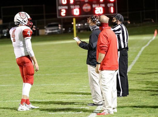PLAY CALL – Red Devils head coach Eric Knott (center) looks over his play sheet, as quarterback Bryce Harper waits for the call. South Fulton posted their first win of the year Friday night at Fulton County, beating the Pilots 6-0 in overtime. (Photo by Charles Choate)