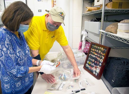 Discovery Park docent Lisa Sears and security guard Randy Anding look over the campaign buttons that will be on display beginning Oct. 8. Anding began collecting campaign buttons in the mid-1970s after a visit to Jimmy Carter's campaign headquarters. (Photo submitted)