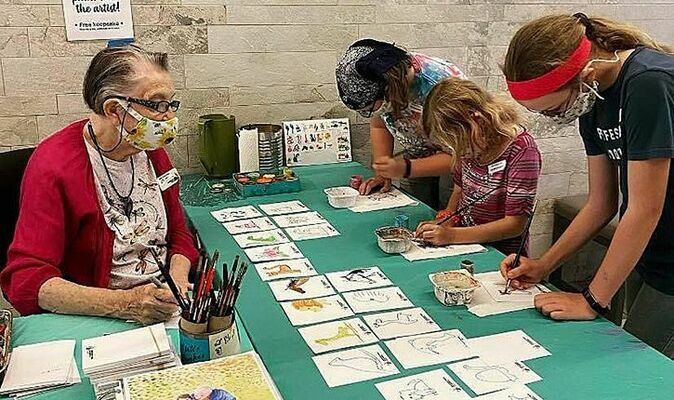 Discovery Park of America volunteer Marti Doss paints with guests. Doss has been a volunteer for the park since it opened in 2013. (Photo submitted)