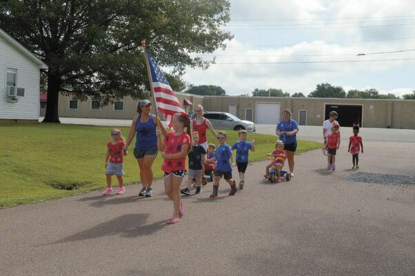 FOR THE RED, WHITE AND BLUE – Children who attend Ms. Angela's Little Angels childcare in South Fulton, display their patriotism in an Independence Day parade through the neighborhood, featured in the Current July 8.
