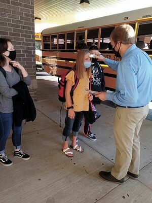 TEMP CHECK – As featured on page one of the Aug. 19 edition of The Current, South Fulton Middle School teacher David Whitesell assisted in checking temperatures of SFMS/SFHS students as they exited the bus to begin classes Aug. 17, with masks required.