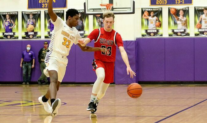 KEEP AWAY – South Fulton's Bryce McFarland keeps a Union City Tornado at bay Jan. 12, on a road trip. The Red Devils did not get the win, with Union City pulling away, 57-38. (Photo by Jake Clapper)
