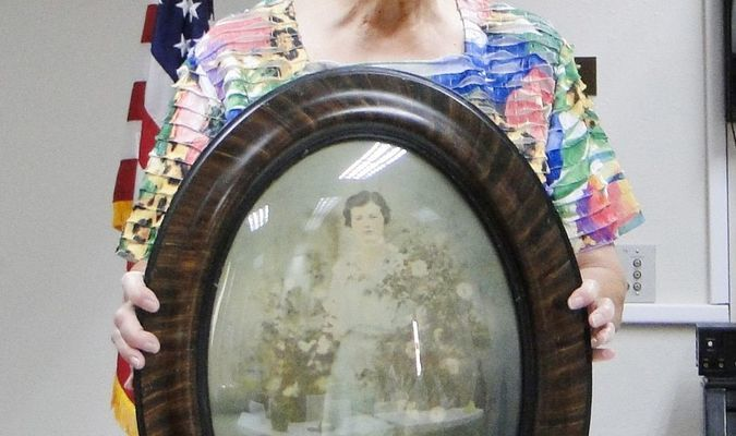 Jan Crow displays unusual curved photo, with curved glass, of her ancestor. (Photo by Tom Tyler)