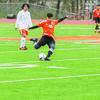 Aaron DeJulian boots the ball hard to send it to teammates set up near Mineola goal Saturday.