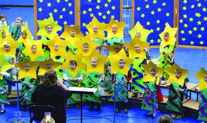 Pre-schoolers dressed as Christmas trees.