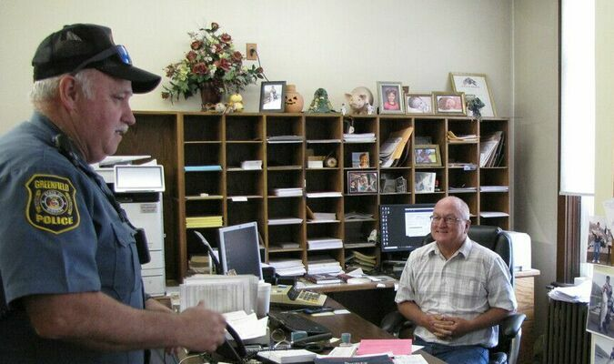 """Greenfield Police Chief Tim Larking delivers a subpoena to Dade County Collector Rod O'Connor to obtain the """"real line-up"""" of county players in the upcoming city-county benefit softball game. (Photo by James McNary)"""