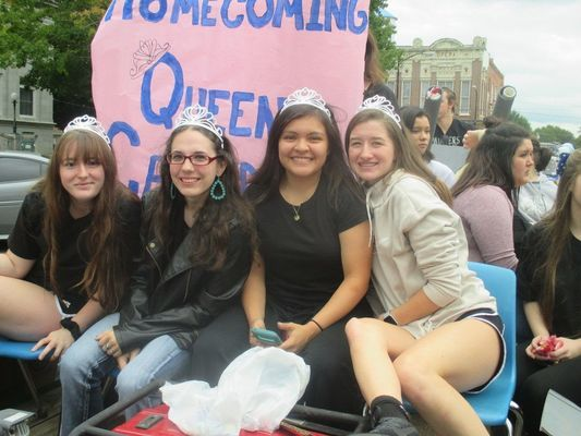 Homecoming queen candidates make themselves comfortable at the front of their float.