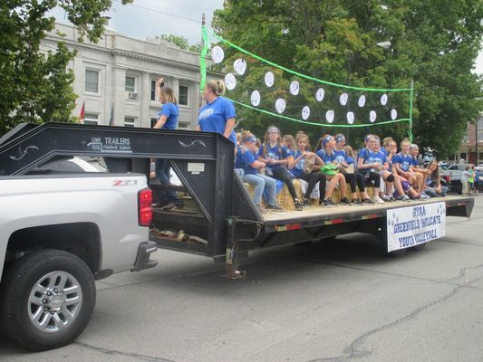 GYAA Volleyball teams and coaches ride on a float adorned with a volleyball net.