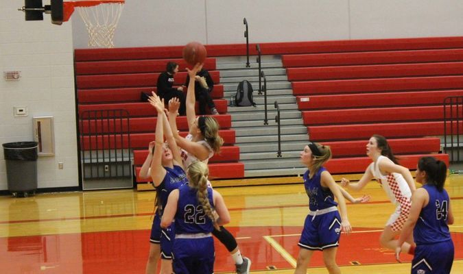 Miller's Kaylee Helton puts up a shot over Greenfield defenders.  (Photo by Austin Bunn)